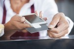 Salesman Swiping Credit Card On Mobile Phone